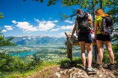 Due viandanti femminili che godono della vista splendida sopra il lago hanno sanguinato ed alpi il giorno di estate Fotografia Stock