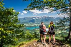 Due viandanti femminili che godono della vista splendida sopra il lago hanno sanguinato ed alpi il giorno di estate Immagine Stock Libera da Diritti