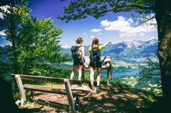 Due viandanti femminili che godono della vista splendida sopra il lago hanno sanguinato ed alpi il giorno di estate Fotografie Stock
