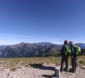 Due viandanti maschii stanno indicando alle montagne lontano e stanno parlando di che cosa i nomi dei quei montagna sono Fotografia Stock Libera da Diritti