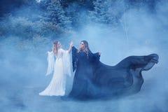 Due yin yang delle donne nella nebbia Il mago scuro incontra Elf leggero una strega Le streghe vigorose stanno ballando nel Fotografie Stock