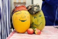 Due zucche gialle con i fronti dipinti della donna e dell'uomo con lo strappo Fotografia Stock