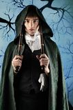 Duel. Portrait of a young gentlemen in a dinner jacket and cloak holding guns in his hands. Shot in a studio Stock Image