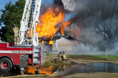 Duel Attack. A fireman at the controls of an aerial truck ladder fights a blaze with two other firefighters on the ground Stock Photos