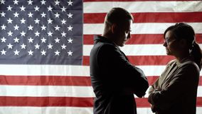 Duel of views. Silhouettes of men and women on the background of the American flag