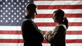 Duel of views. Silhouettes of men and women on the background of the American flag.