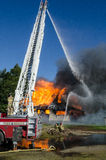 Dueling Hoses. Firemen attack a burning house with water from a ladder above and on the ground Stock Image