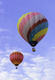 Duelling Hot Air Balloons. Two hot air balloons in a game of hare and hound in the sky with a blue sky and fluffy white clouds Royalty Free Stock Image