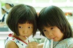 Duelling Straws. Two cute young Asian girls lean their heads together and sip from straws as they share a drink (cup not shown Stock Photos