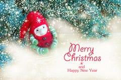 Duende colorido bonito do brinquedo do Natal ao lado dos ramos naturais frescos da árvore de Natal em um fundo de madeira fotos de stock royalty free