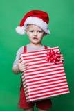 Duende de la Navidad que sostiene la caja de regalo roja grande con la cinta Ayudante de Santa Claus Imagenes de archivo