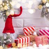 Duende, envuelto regalos de Navidad, ramas de árbol de la piel en el tex blanco fotografía de archivo