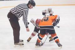 Duende malicioso que juega entre los jugadores de los equipos del hielo-hockey Foto de archivo libre de regalías