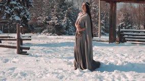 Duende oscuro que se prepara para la guerra, muchacha oscuro-cabelluda valiente en impermeable que vuela gris largo en la nieve b almacen de metraje de vídeo