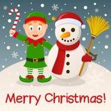 Duende y muñeco de nieve de la Navidad en la nieve Imagen de archivo