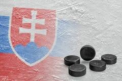 Duendes maliciosos de hockey y la imagen de la bandera eslovaca en el hielo Fotos de archivo libres de regalías