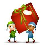 Duendes que llevan el regalo de la Navidad Imagen de archivo libre de regalías