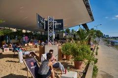 DUESSELDORF, ALEMANIA - 17 DE AGOSTO DE 2016: los visitantes no identificados gozan del sol en un club de la playa debajo del cin Foto de archivo libre de regalías