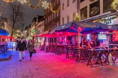 DUESSELDORF, GERMANIA - NOVEMBERT 28, 2017: I pedestrants di Unidentifeied popolano i supporti all'aperto illuminati della birra  Fotografie Stock