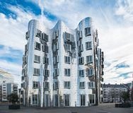 DUESSELDORF, GERMANY - JANUARY 20, 2017: One of the famous Ghery-Buildings in the New Media Harbor contrasts with the vivid sky in Stock Photos