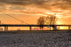 DUESSELDORF, GERMANY - JANUARY 20, 2017: The winter sun goes down over a large bridge and bathes everything in orange warm light Stock Images