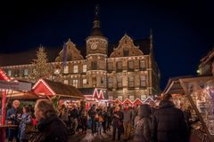 DUESSELDORF, GERMANY - NOVEMBERT 28, 2017: Unidentifeied pedestrants populate the illuminated Christmas market on the. Burgplatz in front of the historic town Royalty Free Stock Photos
