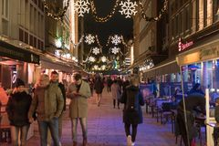 DUESSELDORF NIEMCY, LISTOPAD, - 28, 2017: Unidentifeied pedestrants zaludniają iluminującego starego miasteczko z stołami wciąż s fotografia stock