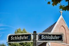DUESSELDORF TYSKLAND - AUGUSTI 17, 2016: Den Schlossufer adressen skrivs ut på ett dubbelt gatatecken på Rhenpromenaden Royaltyfria Bilder