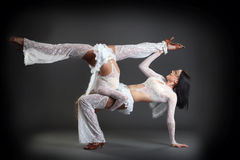 Duet of flexible slim dancers posing in studio Stock Photography