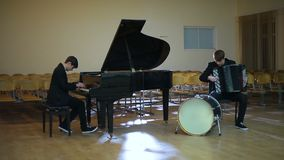 Duet pianist and accordionist playing music in empty room stock footage