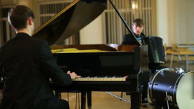 Duet pianist and accordionist playing music in empty room stock video footage