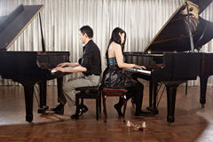 Duet with pianos. Two people, a couple playing duet musical performance with two grand pianos Stock Photo