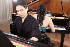 Duet with pianos. Two people, a couple playing duet musical performance with two grand pianos Royalty Free Stock Image