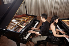 Duet with pianos. Two people, a couple playing duet musical performance with two grand pianos Royalty Free Stock Photography