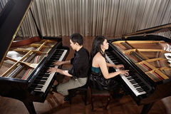 Duet with pianos. Two people, a couple playing duet musical performance with two grand pianos Royalty Free Stock Photos
