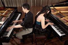 Duet with pianos. Two people, a couple playing duet musical performance with two grand pianos Stock Image