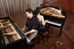 Duet with pianos. Two people, a couple playing duet musical performance with two grand pianos Royalty Free Stock Images