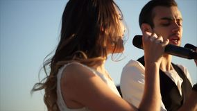 Duet singing a song outdoor. Slow motion shot of young man and woman singing a duet during outdoor musical festival stock footage