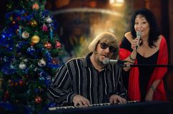 Duet of two old musicians sings Christmas carols. Man and women sing duets at Christmas songs. Man in light yellow wig plays electric piano. Mature women in big royalty free stock images