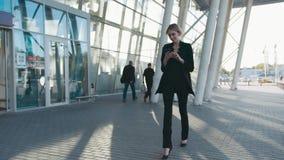 Dufna gorąca młoda blondynki dziewczyna w eleganckim formalnym czarnym kostiumu chodzi lotniskowym terminal i używa ona zdjęcie wideo