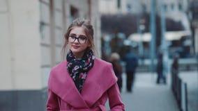 Dufna młoda kobieta chodzi samotnego puszek w eleganckim stroju zatłoczona ulica Elegancki spojrzenie, chłodno ostrzyżenie, i zbiory