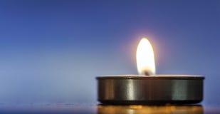 Duftendes Kerzenlicht über blauem Hintergrund Stockbilder