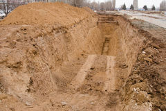 Dug a pit, trench. The newly dug Foundation pit or underground utilities royalty free stock photo