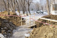 Dug trench  with fence tape and  wooden bridge above. Stock Photography