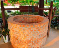 Dug water well is a structure created in the ground by digging to access groundwater in underground aquifers. The well water is drawn by hand winch using the stock photo