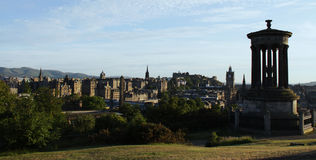 Dugald Stewart monument and Edinburgh skyline. Edinburgh skyline. From left to right,  the pentland hills, the top of St Giles cathedral, Edinburgh castle, and Stock Image