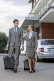 Długi biznesowa para z bagażu odprowadzeniem na zewnątrz hotelu Obrazy Stock