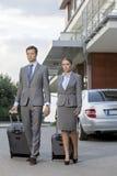 Długi biznesowa para z bagażu odprowadzeniem na zewnątrz hotelu Obrazy Royalty Free