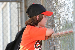 In the dugout. Young baseball player watching the game from the dugout Royalty Free Stock Photography