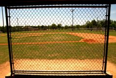 In the dugout at baseball field. Chain link fence in the dugout on a baseball field royalty free stock images